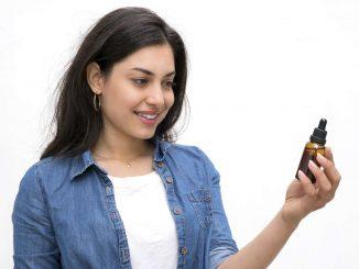 בחורה מחזיקה בקבוק שמן CBD ביד